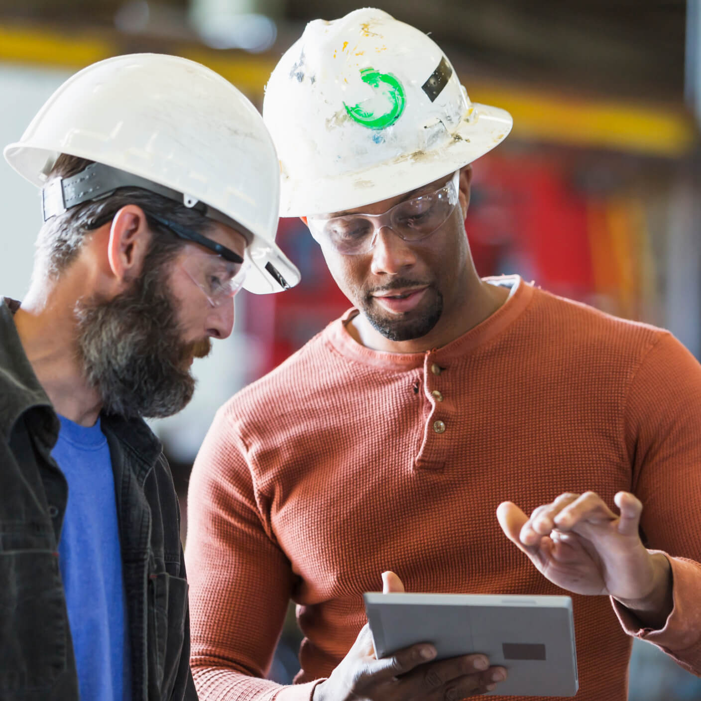 two workers wearing hard hats looking at an ipad