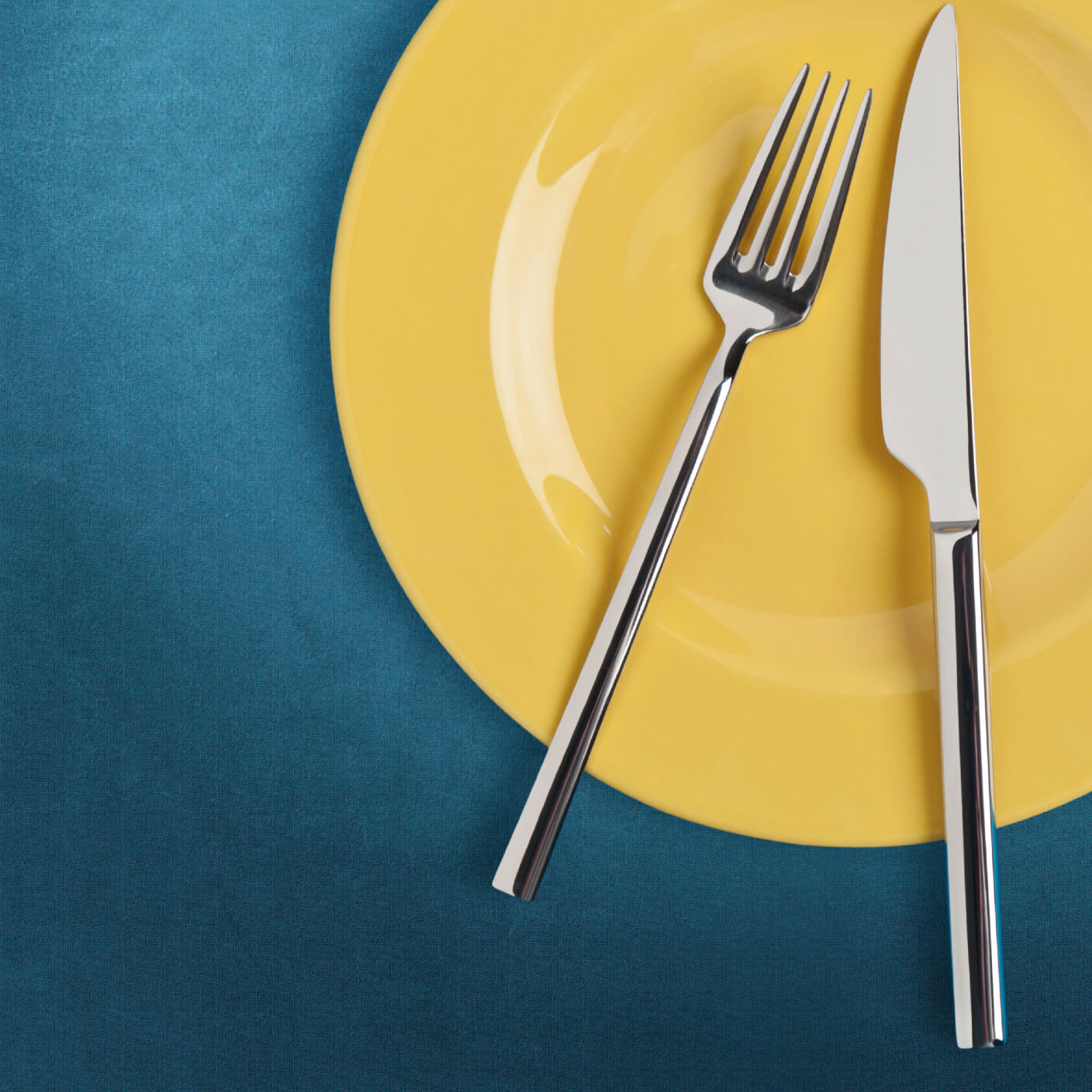 Place Setting with Yellow Plate and a Knife and Fork