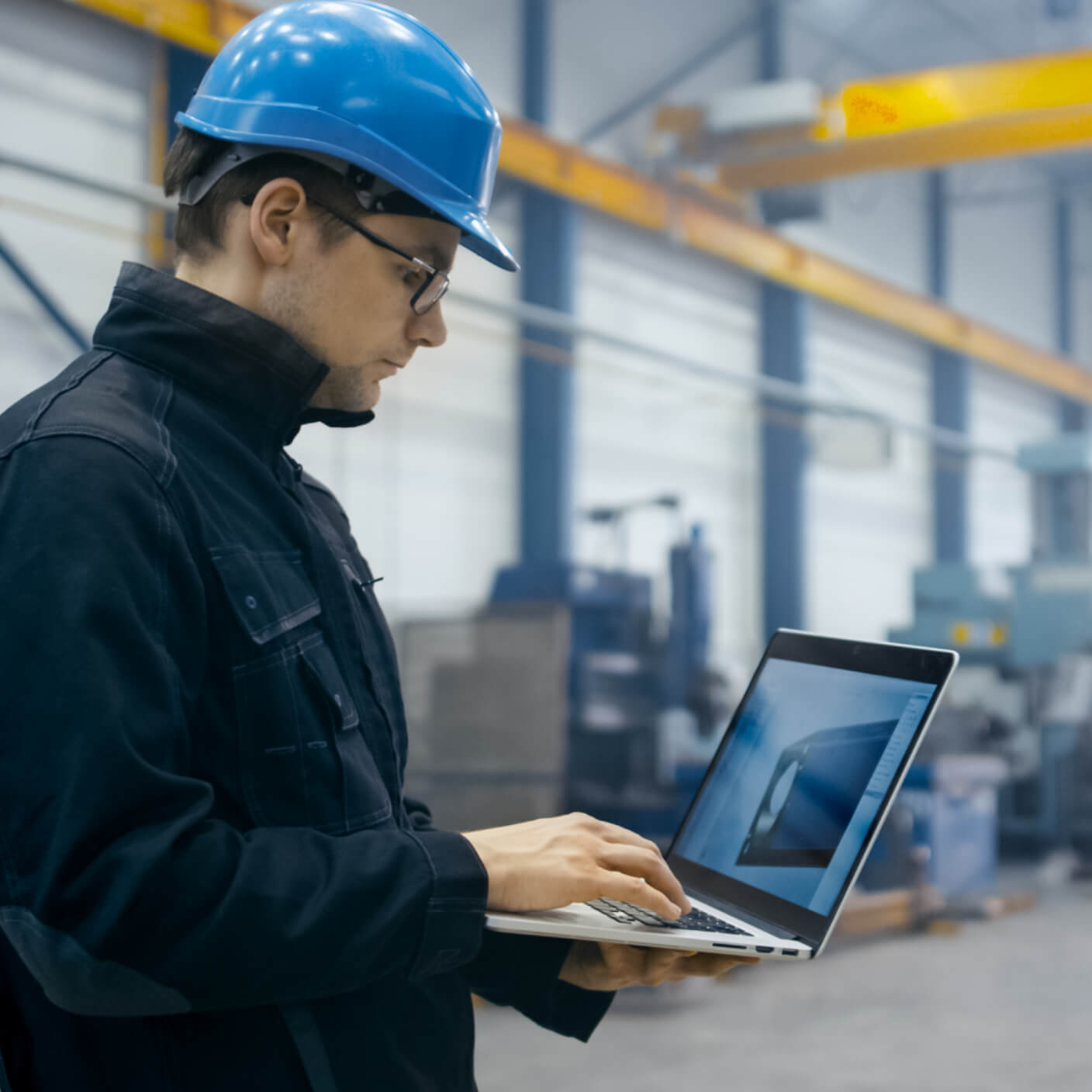 worker in industrial setting with hardhat and laptop